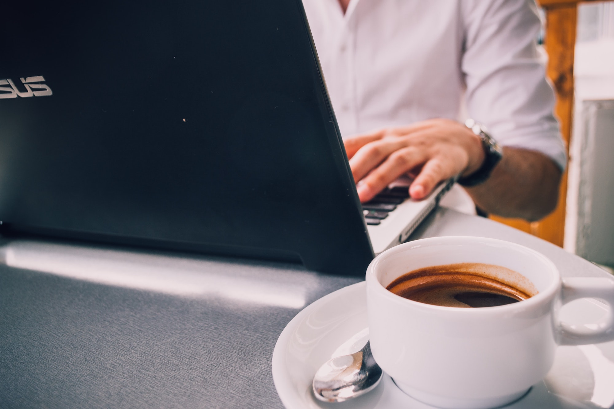 man sitting at table with coffee and laptop